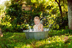Boy watered. Boy splashing in the water stock photo