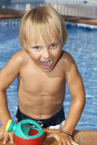 Boy with watering can in the swimming pool Royalty Free Stock Images