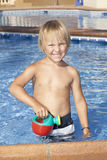 Boy with watering can in the swimming pool Stock Image