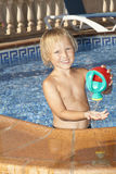 Boy with watering can in the swimming pool Royalty Free Stock Photography