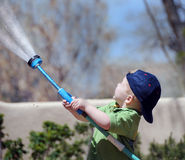 Boy watering the garden. A small boy holding a garden hose, spraying water  up in the sky Royalty Free Stock Photography