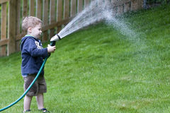 Boy watering garden Royalty Free Stock Photos