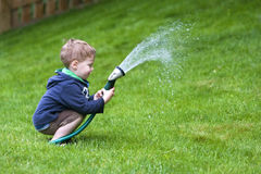 Boy watering garden Royalty Free Stock Photo