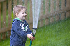 Boy watering garden Stock Photography