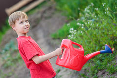 Boy watering garden Stock Image