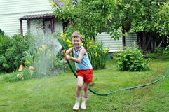 Boy watering lawn with hose. Cute smiling boy watering lawn with hose Royalty Free Stock Photo