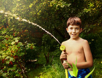Boy with watering pipe on the green garden background Stock Images