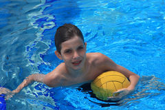 Boy with a waterpolo ball. Boy with waterpolo ball in a pool Royalty Free Stock Image