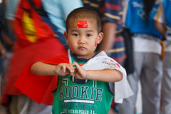 Boy waves Chinese and Olympic flags Royalty Free Stock Images
