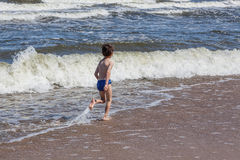 Boy and waves Royalty Free Stock Image