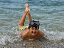 Boy and the waves at sea. Boy with scuba mask on his head lying in the Adriatic sea in shallow water - enjoying in summer vacations - spending holidays at the royalty free stock photography
