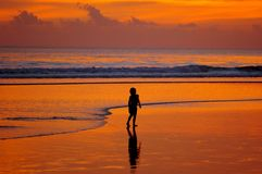 Boy with waves at sunset Stock Photo