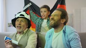 Boy waving German flag, family watching national football team match at home. Stock footage stock footage