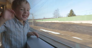 Boy Waving Hand out of the Train Window. Little boy is standing by the window of moving train and waving hand stock video footage