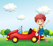 A boy waving his hand beside a car Stock Image