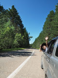 Boy waving from the moving car. travel concept Royalty Free Stock Photos