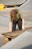 Boy Waxing Rail. Male teen skateboarder with dreadlocks waxing rail at skate park Stock Images