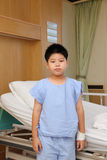 Boy wear patient suit standing  in front of hospital bed Royalty Free Stock Photos