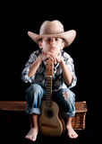 A boy wearing. A hat with a guitar on a black background Royalty Free Stock Photo