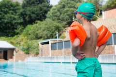 Boy wearing arm band standing at poolside Stock Images