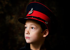 Boy wearing band hat. Portrait of a young boy wearing a red and black marching band hat.  Black background Royalty Free Stock Photos