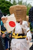 Boy wearing a basket mask. Young boy wearing a full face mask woven from wicker and carrying a paper fan performs in an agricultural festival in Southern Japan royalty free stock images