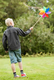 Boy wearing black jacket holds colorful whirligig Royalty Free Stock Photography