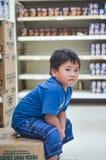 Boy Wearing Blue Crew-neck T-shirt Sitting on Cardboard Box Royalty Free Stock Image