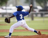 Boy Wearing Blue and White 3 Jersey About to Pitch a Baseball Royalty Free Stock Photo