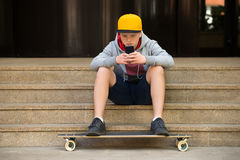 Boy Wearing Cap Looking At Cellphone Royalty Free Stock Photography