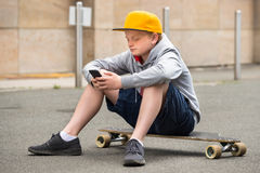 Boy Wearing Cap Using Smartphone royalty free stock images