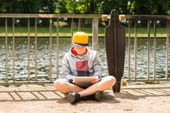 Boy Wearing Cap Using Digital Tablet royalty free stock image