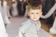 Boy wearing classic shirt standing in church during wedding ceremony stock photography
