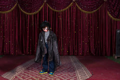 Boy Wearing Clown Make Up and Large Coat on Stage Stock Photography