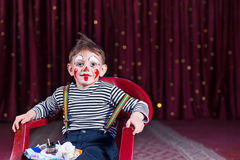 Boy Wearing Clown Makeup Sitting in Chair on Stage Royalty Free Stock Images