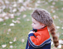 Boy wearing coat and hat. A young child standing out in the cold, wearing a warm jacket and a raccoon hat Stock Photography