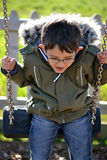 Boy wearing coat on swing. Boy wearing glasses and winter coat playing on swing Stock Photo