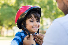 Boy wearing cycle helmet. Father helping cheerful son wearing helmet for cycle. Excited little boy getting ready by wearing bike helmet to start cycling. Happy Stock Photography