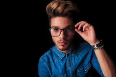 Boy wearing denim posing while fixing his glasses Royalty Free Stock Photography
