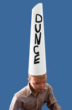 Boy wearing dunce cap. Boy mannequin wearing dunce cap against blue background Stock Photography