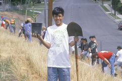 A boy wearing an Earth Day t-shirt participating in a tree planting by the Clean & Green volunteers of the Los Angeles Conservatio Royalty Free Stock Photos