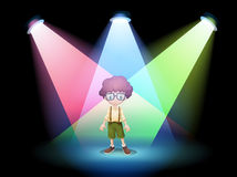 A boy wearing an eyeglass standing on the stage with spotlights Stock Photography