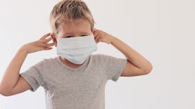 Boy wearing facial disposable mask to avoid viral infection.