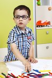 Boy wearing glasses and draw with crayons Royalty Free Stock Photo