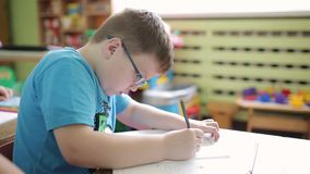 A boy wearing glasses in elementary school writes in pencil in a notebook and solves the problem of logic and