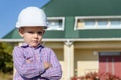 Boy Wearing Hard Hat Presenting Finished House Stock Image