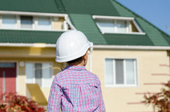 Boy Wearing Hard Hat Standing in front of House Royalty Free Stock Photo