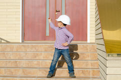 Boy Wearing Hard Hat on Steps Looking Back Stock Photography