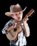 Boy wearing a hat with. A boy wearing a hat with a guitar on a black background Stock Photos