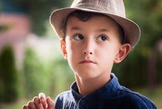 Boy wearing hat posing. In the garden royalty free stock photo